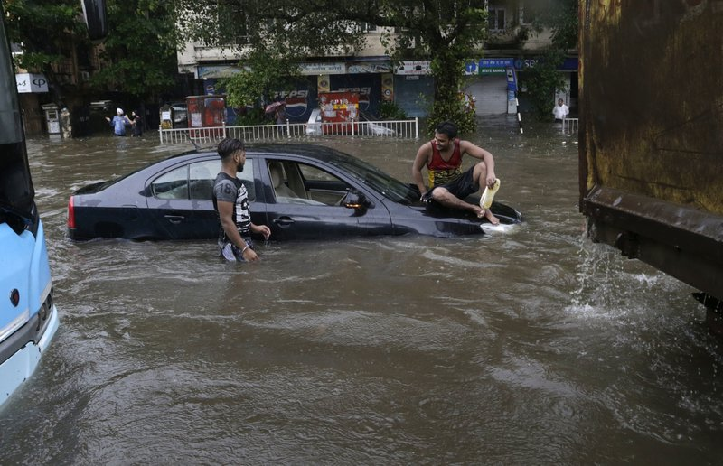 A man sits on a car that got stuck in a waterlogged street following heavy rains in Mumbai, India, Tuesday, Aug. 29, 2017. Heavy rains Tuesday brought Mumbai to a halt flooding vast areas of the city.