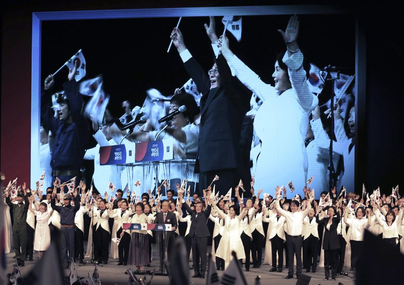 "In this South Korean President Moon Jae-in, bottom center gives three cheers for his country during a ceremony to celebrate Korean Liberation Day, at Seong Cultural Center in Seoul, South Korea. Moon, in a televised speech Tuesday on the anniversary of the end of World War II and the Korean Peninsula's liberation from Japanese colonial rule, said that Seoul and Washington agree that the crisis over the North's nuclear program should ""absolutely be solved peacefully,"" and that no U.S. military action on the Korean Peninsula could be taken without Seoul's consent."