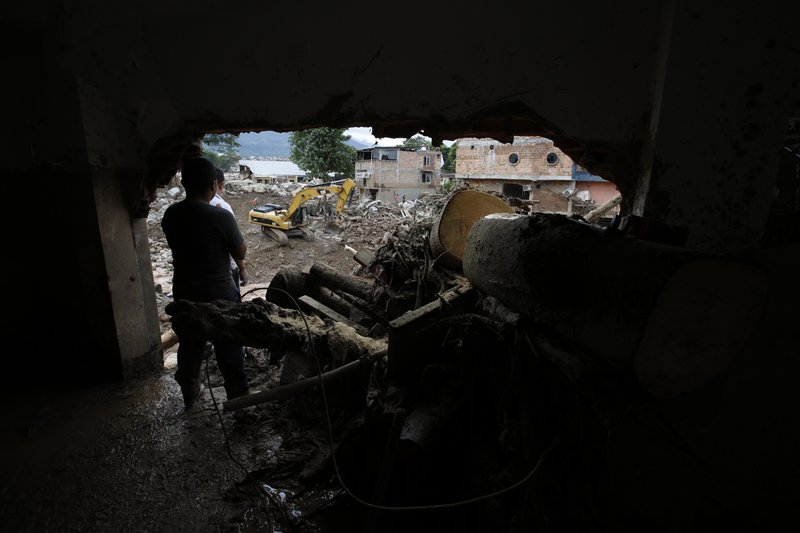 A man removes mud from his damage house in Mocoa, Colombia, Sunday, April 2, 2017. A grim search for the missing resumed at dawn Sunday in southern Colombia after surging rivers sent an avalanche of floodwaters, mud and debris through a city, killing at least 200 people and leaving many more injured and homeless.