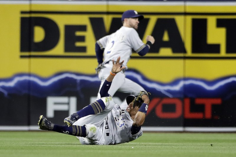 Milwaukee Brewers center fielder Keon Broxton, below, falls after missing a hit for an RBI triple by the San Diego Padres' Luis Perdomo during the second inning of a baseball game Monday, May 15, 2017, in San Diego. (AP Photo/Gregory Bull)