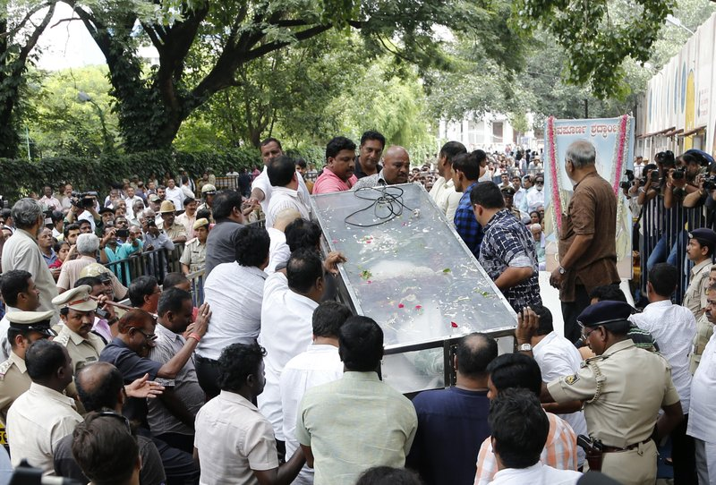 Mourners and others place the casket of Indian journalist Gauri Lankesh for public viewing in Bangalore, India, Wednesday, Sept. 6, 2017. The Indian journalist was gunned down outside her home the southern city of Bangalore — the latest in a string of deadly attacks targeting journalists or outspoken critics of religious superstition and extreme Hindu politics.