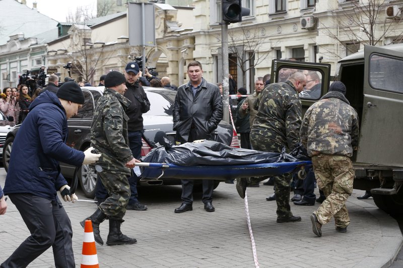 Forensic experts carry the body of Denis Voronenkov, after he was shot dead in Kiev, Ukraine, Thursday, March 23, 2017. Ukrainian police said Voronenkov was shot dead Thursday by an unidentified gunman at the entrance of an upscale hotel in the Ukrainian capital. Voronenkov, 45, a former member of the communist faction in the lower house of Russian parliament, had moved to Ukraine last fall and had been granted Ukrainian citizenship.