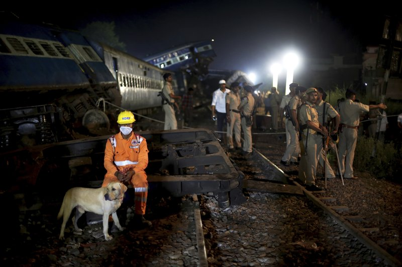 A rescuer from national disaster response forces (NDRF) takes a break from rescue operations next to the upturned coaches of the Kalinga-Utkal Express after an accident near Khatauli, in the northern Indian state of Uttar Pradesh, India, Sunday, Aug. 20, 2017. Six coaches of a passenger train derailed in northern India on Saturday, killing more than 20 people and injuring dozens, officials said.