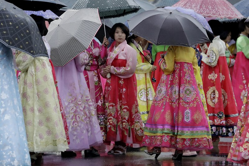 University students wearing traditional Korean dresses wait in the rain for the start of a group dance on Thursday, July 27, 2017, in Pyongyang, North Korea as part of celebrations for the 64th anniversary of the armistice that ended the Korean War.