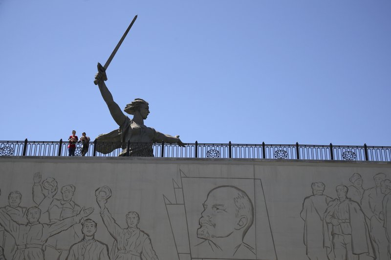 In this June 17, 2018 photo tourists visit the Motherland Calls monument as the portrait of Soviet founder Vladimir Lenin is seen on the wall in front during the 2018 soccer World Cup in Volgograd, Russia. The monument commemorates the victims of the Battle of Stalingrad, in which the Red Army turned back Nazi Germany's army in Volgograd.