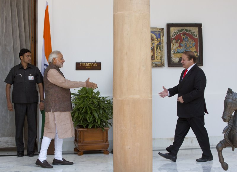 In this May 27, 2014 file photo, Indian Prime Minister Narendra Modi, left, walks to shake hand with his Pakistani counterpart Nawaz Sharif before the start of their meeting in New Delhi, India. Modi began his term on a conciliatory note by inviting his Pakistani counterpart, again Nawaz Sharif, to his oath-taking ceremony. The next year, Modi paid a surprise visit to Sharif's home in Lahore. But the friendliness dissolved days later when gunmen, allegedly from Pakistan, killed seven soldiers at an Indian air force base. As the 70th anniversary of India-Pakistan Partition comes up next week, relations between the two nations are as broken as ever. In some ways, their violent birth pangs dictated their future course through suspicion and animosity.