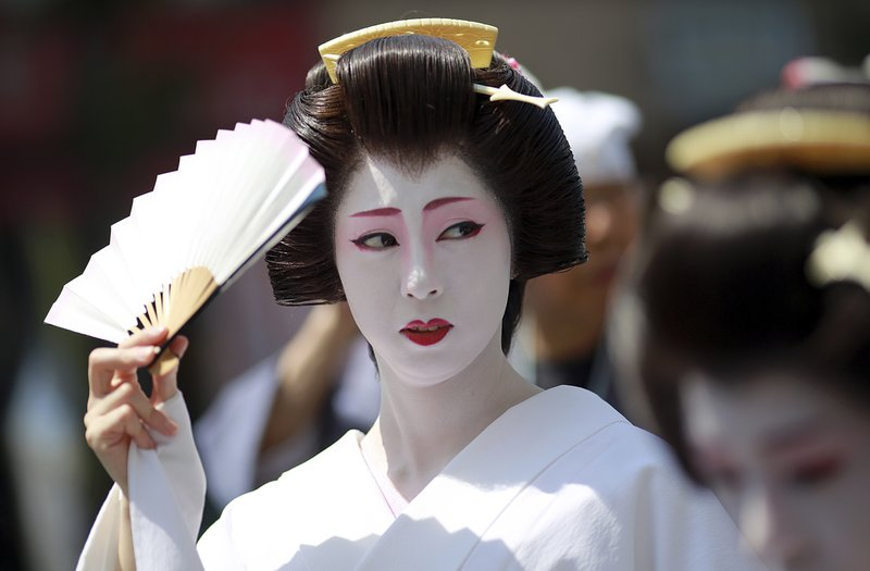 In this Friday, May 19, 2017, photo, a woman in traditional geisha dress uses a fan to block the sun as she joins others to parade down the street to Asakusa Shrine in the compound of Sensoji Temple prior to the annual Sanja Festival, one of the three major festivals in Tokyo.