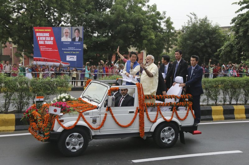 Japanese Prime Minister Shinzo Abe, center left, accompanied by Indian Prime Minister Narendra Modi, center rides in an open vehicle through the streets of Ahmadabad, India, Wednesday, Sept. 13, 2017. Abe is on a two-day visit to India.