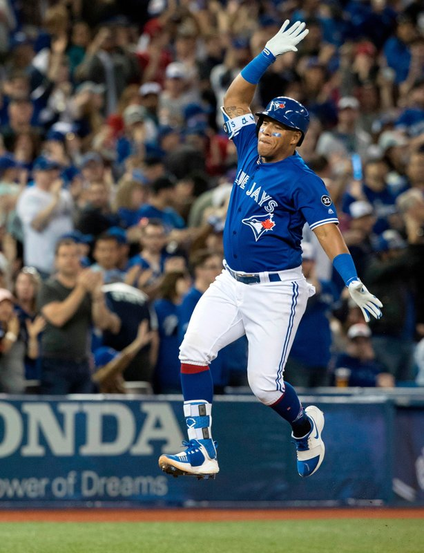 Toronto Blue Jays Yangervis Solarte leaps in air rounding third base after hitting a solo home run against the New York Yankees