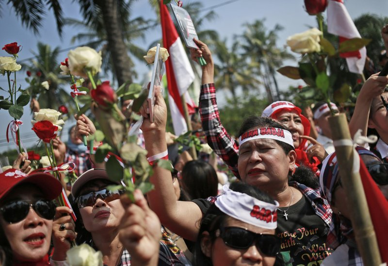 "Supporters of Jakarta Governor Basuki ""Ahok"" Tjahaja Purnama hold flowers during a rally outside the court where his sentencing hearing is held in Jakarta, Indonesia, Tuesday, May 9, 2017. The minority Christian governor is currently on trial on accusation of blasphemy following his remark about a passage in the Quran that could be interpreted as prohibiting Muslims from accepting non-Muslims as leaders."