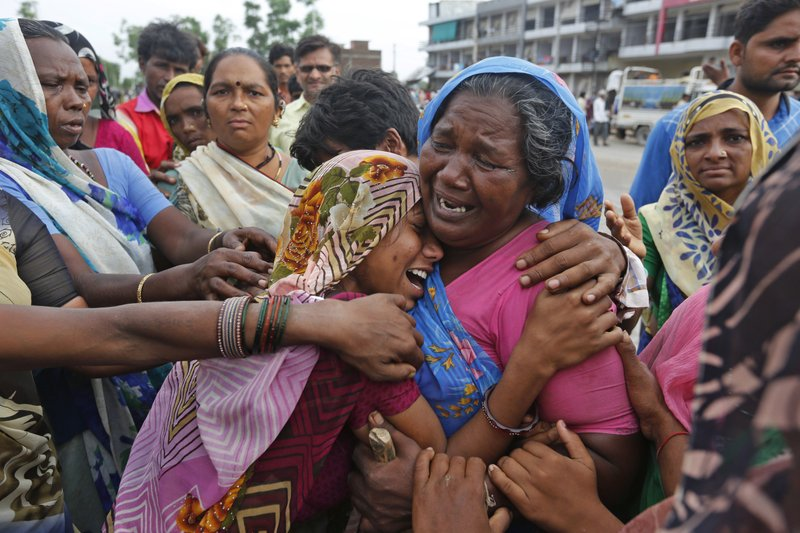 In this Wednesday, July 26, 2017, file photo, Indian flood victim are overcome with emotion after they met at a camp for the displaced in Thara in Banaskantha district, Gujarat, India. Dozens have died in the state of Gujarat amid torrential rains. The monsoon season runs from June through September.
