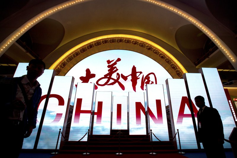 In this Thursday, Sept. 28, 2017, file photo, visitors walk past video display boards at an exhibition highlighting China's achievements under five years of leadership by Chinese President Xi Jinping at the Beijing Exhibition Hall in Beijing. The exhibition comes ahead of a Communist Party congress in October during which Xi is expected to be confirmed for a second five-year term as China's head of state.