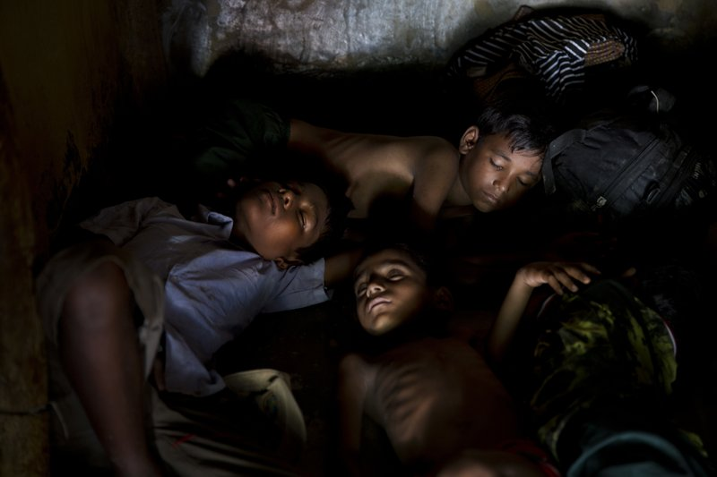 In this Sunday, Sept. 24, 2017, file photo, newly arrived Rohingya Muslim Syed Noor's sons sleep inside their uncle's shelter in Kutupalong refugee camp, Bangladesh. The massive exodus of Rohingya Muslims fleeing Myanmar to escape brutal persecution appears to have slowed down, but several recent refugees say at least tens of thousands more are huddled near beaches or in forests waiting to escape.
