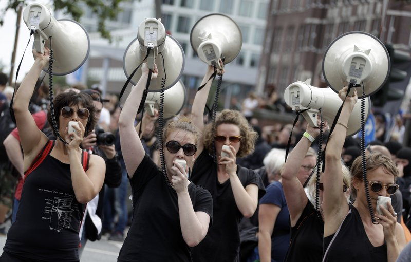 Women hold up megaphones during a protest against the G-20 summit in Hamburg, northern Germany, Saturday, July 8, 2017. The leaders of the group of 20 meet July 7 and 8.