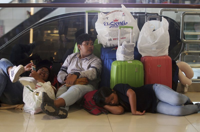 Tourists rest as Ngurah Rai International Airport is closed due to the eruption of Mount Agung in Bali, Indonesia Friday, June 29, 2018. The Indonesian tourist island of Bali closed its international airport Friday, stranding thousands of travelers, as the Mount Agung volcano gushed a 2,500-meter (8,200-feet) column of ash and smoke.