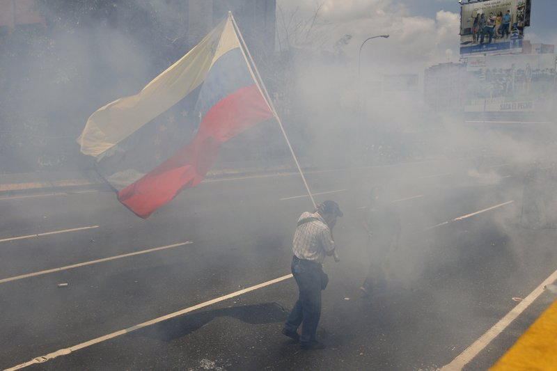 A man carries a Venezuelan flag amid tear gas launched by security forces blocking opponents of President Nicolas Maduro from marching to the Ombudsman's office in downtown Caracas, Venezuela, Wednesday, April 26, 2017. Hundreds of thousands of Venezuelans have flooded the streets over the last month to demand an end to Maduro's presidency.