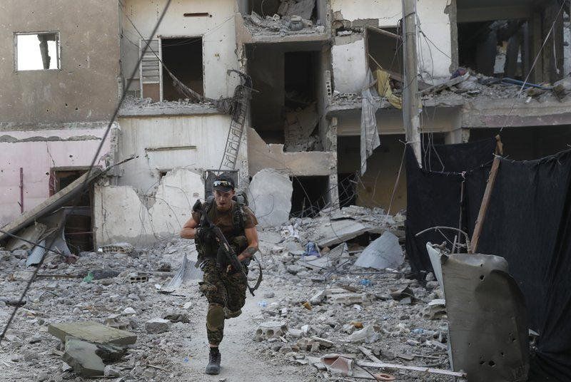 A U.S.-backed Syrian Democratic Forces fighter runs in front of a damaged building as he crosses a street on the front line, in Raqqa city, Syria, Thursday, July 27, 2017. U.S.-backed Syrian fighters have captured almost half of the Islamic State group's de facto capital of Raqqa, but the push into the northern city has slowed due to stiff resistance and large amounts of explosives planted by extremists, a spokeswoman for the fighters and monitors said Thursday.