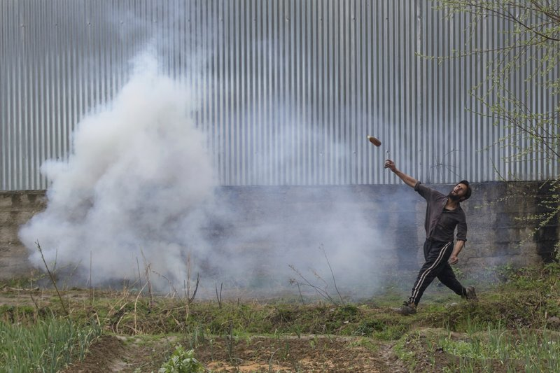 A Kashmiri protester throws a glass bottle at Indian security forces during a protest near the site of a gun battle in Chadoora town, about 25 kilometers (15 miles) south of Srinagar, Indian controlled Kashmir, Tuesday, March 28, 2017. Three civilians were killed and 28 other people were injured in anti-India protests that erupted Tuesday following a gunbattle between rebels and government forces that killed a rebel in disputed Kashmir, police and witnesses said. The gunbattle began after police and soldiers cordoned off the southern town of Chadoora following a tip that at least one militant was hiding in a house, said Inspector-General Syed Javaid Mujtaba Gillani. As the fighting raged, hundreds of residents chanting anti-India slogans marched near the area in an attempt to help the trapped rebel escape.