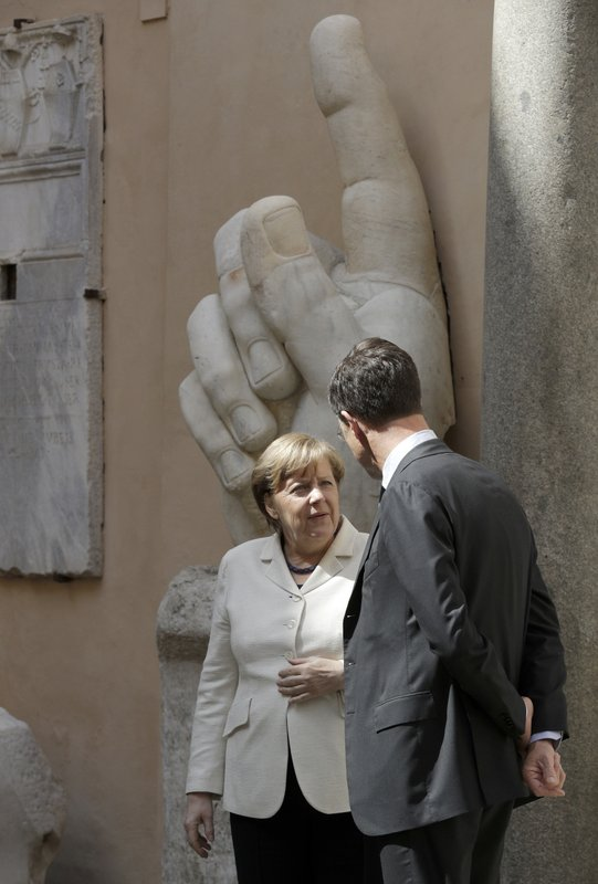 German Chancellor Angela Merkel, left, speaks with Dutch Prime Minister Mark Rutte after a group photo in the Cortile di Michelangelo during an EU summit in Rome on Saturday, March 25, 2017. EU leaders were gathering in Rome to mark the 60th anniversary of their founding treaty and chart a way ahead following the decision of Britain to leave the 28-nation bloc. In the background the remaining marble right hand of the Colossus of Constantine (312-315 AD).