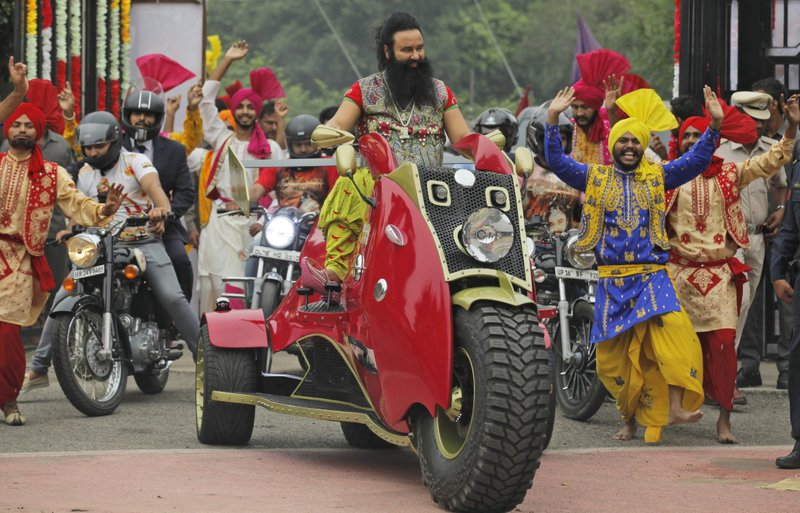 "In this Wednesday, Oct. 5, 2016, file photo, Indian spiritual guru, who calls himself Dr. Saint Gurmeet Singh Ram Rahim Insan, rides a motorcycle as he arrives for a press conference ahead of the release of his new film ""MSG: The Warrior Lion Heart,"" in New Delhi, India. A judge on Monday, Aug. 28, 2017, sentenced the flamboyant and controversial Indian spiritual guru to prison on charges of raping two female followers."
