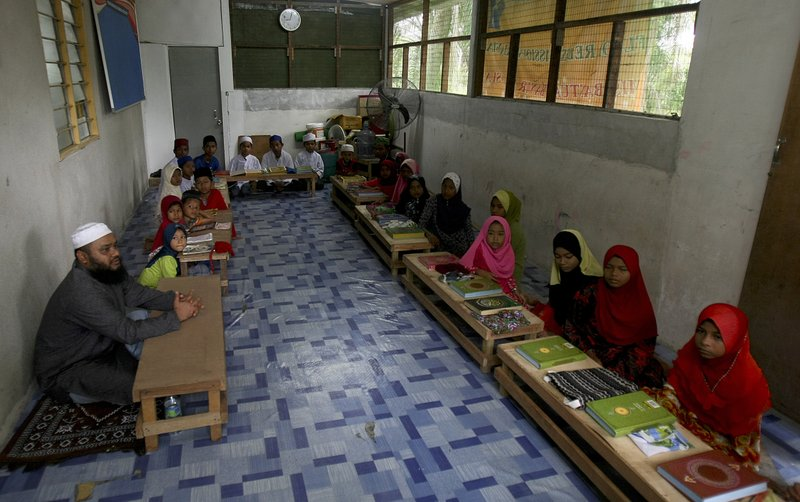 In this Tuesday, Sept. 12, 2017, photo, Rohingya Muslim children living in Malaysia recite from the holy Quran at a school in Klang, on the outskirts of Kuala Lumpur, Malaysia. Recent violence in Myanmar has driven hundreds of thousands of Rohingya Muslims to seek refuge across the border in Bangladesh. There are some 56,000 Rohingya refugees registered with the U.N. refugee agency in Malaysia, with an estimated 40,000 more whose status has yet to be assessed.