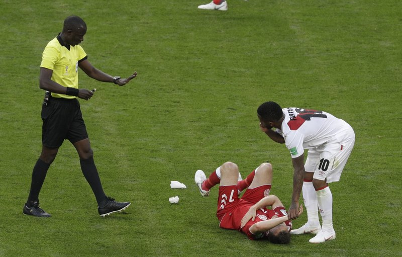 Denmark's William Kvist lies on the pitch as Peru's Jefferson Farfan, right holds his hand as referee Bakary Gassama from Gambia, left, looks on during the group C match between Peru and Denmark at the 2018 soccer World Cup in the Mordovia Arena in Saransk, Russia, Saturday, June 16, 2018.