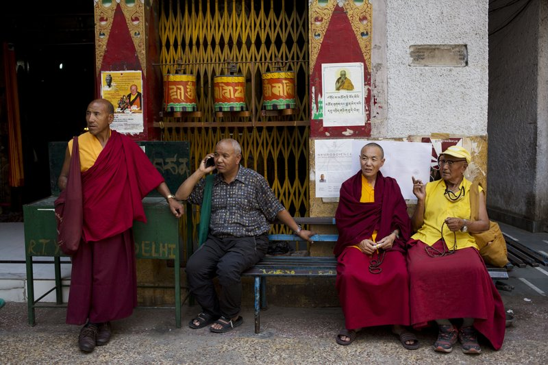 Tibetan monks sit on a bench outside a temple at Majnu Ka Tilla in New Delhi, India, Tuesday, April 4, 2017. India said Tuesday that China should not interfere in its internal affairs, as the Dalai Lama began a weeklong visit to India's remote northeast that Beijing has protested.