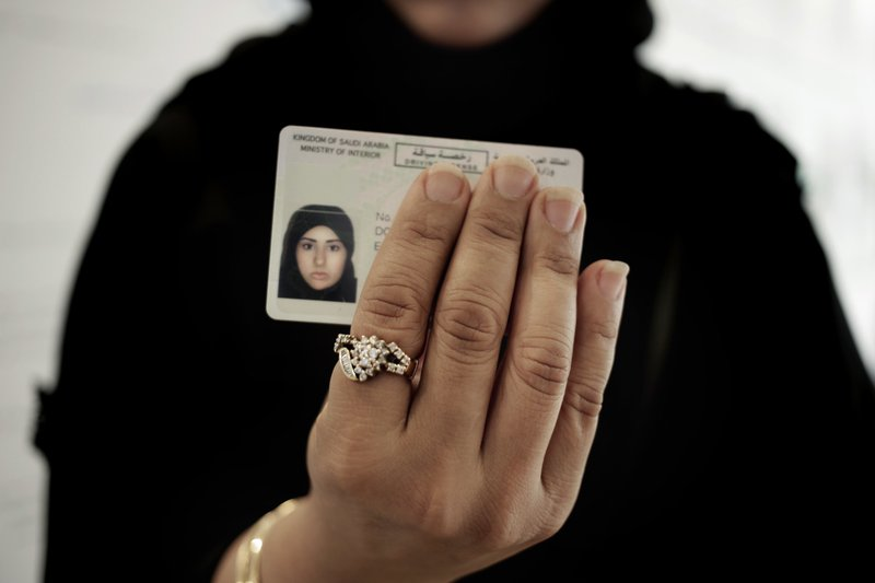 In this June 23, 2018 photo, a Saudi woman covering her name holds her new car license at the Saudi Driving School inside Princess Nora University in Saudi Arabia. As Saudi Arabia prepares to lift a ban on women driving, Saudi women are being pushed to the forefront of a major transformation being spearheaded by the country's Crown Prince Mohammed bin Salman. It also places women in the crosshairs of a decades-old pull-and-tug between Saudis agitating for more social openings and a majority that remains deeply conservative.