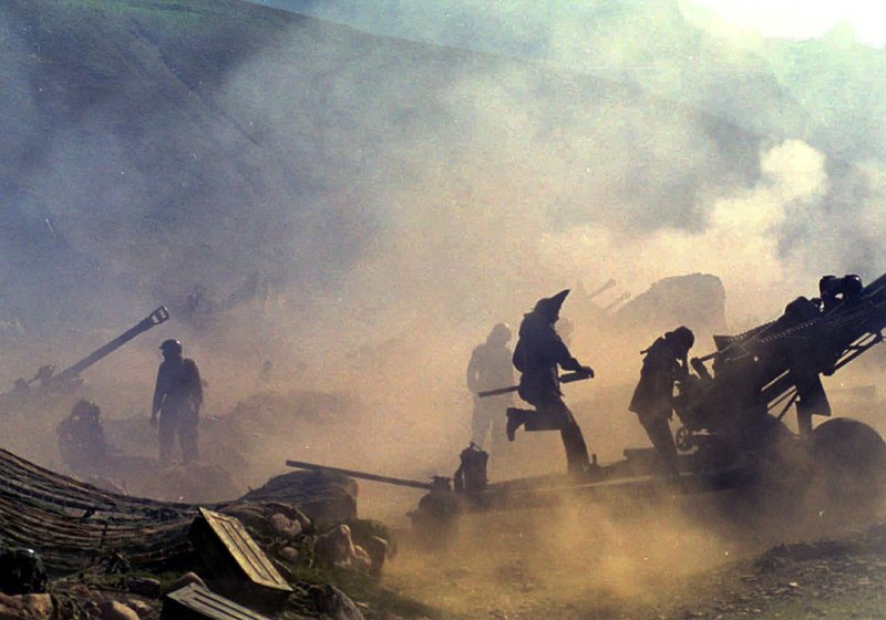 In this July 10, 1999 file photo, Indian artillery guns are engulfed in smoke in Dras, some 155 kilometers (96 miles) north of Srinagar, India as Indian troops fight Pakistani intruders in the disputed Kashmir. In 1999, less than four months after Indian Prime Minister Atal Bihari Vajpayee revived peace talks and took a groundbreaking bus ride to the Pakistani border town of Lahore to meet his Pakistani counterpart, Nawaz Sharif, Sharif's army chief, Gen. Pervez Musharraf, sent armed invaders into Kashmir to capture some mountain peaks. The move provoked two months of air strikes and ground attacks by India, ending after Sharif ordered the fighters to withdraw.