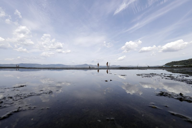 People walk along the shore of Lake Bracciano, about 35 kilometers (22 miles) northwest of Rome, Thursday, July 27, 2017. Rome area's governor last week ordered no more water drawn from Lake Bracciano, which supplies much of the Italian capital, raising risk for staggered water supply shutdowns as long as eight hours daily in alternating neighborhoods. Scarce rain and chronically leaky aqueducts have combined this summer to hurt farmers in much of Italy and put Romans at risk for drastic water rationing starting later this week.