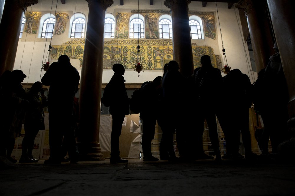 Image: In this Thursday, Dec. 6, 2018 photo, visitors stand bellow a renovated part of a fresco inside the Church of the Nativity, built atop the site where Christians believe Jesus Christ was born, in the West Bank City of Bethlehem. City officials are optimistic that the renovated church will help add to a recent tourism boom and give a boost to the shrinking local Christian population. (AP Photo/Majdi Mohammed)