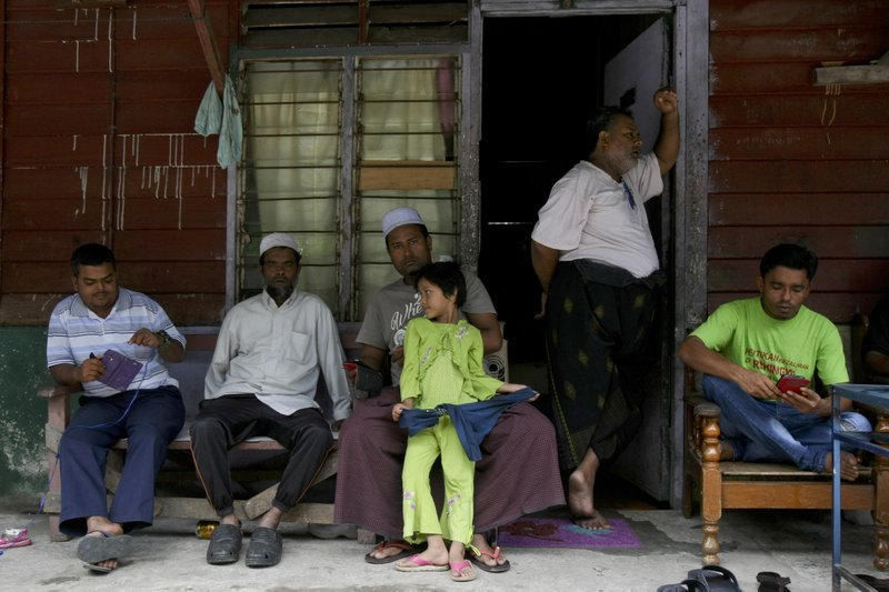 In this Tuesday, Sept. 12, 2017, photo, Rohingya Muslims living in Malaysia rest outside a house in Klang, on the outskirts of Kuala Lumpur, Malaysia. Recent violence in Myanmar has driven hundreds of thousands of Rohingya Muslims to seek refuge across the border in Bangladesh. There are some 56,000 Rohingya refugees registered with the U.N. refugee agency in Malaysia, with an estimated 40,000 more whose status has yet to be assessed.