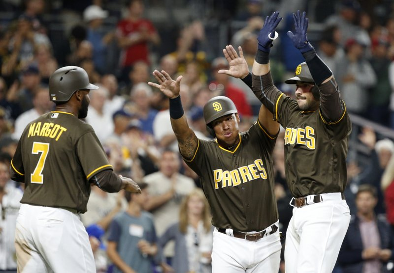 San Diego Padres catcher Austin Hedges, right, celebrates his three-run home run with teammates Manuel Margot, left, and Yangervis Solarte during the seventh inning of a baseball game against the Miami Marlins in San Diego, Friday, April 21, 2017. (AP Photo/Christine Cotter)