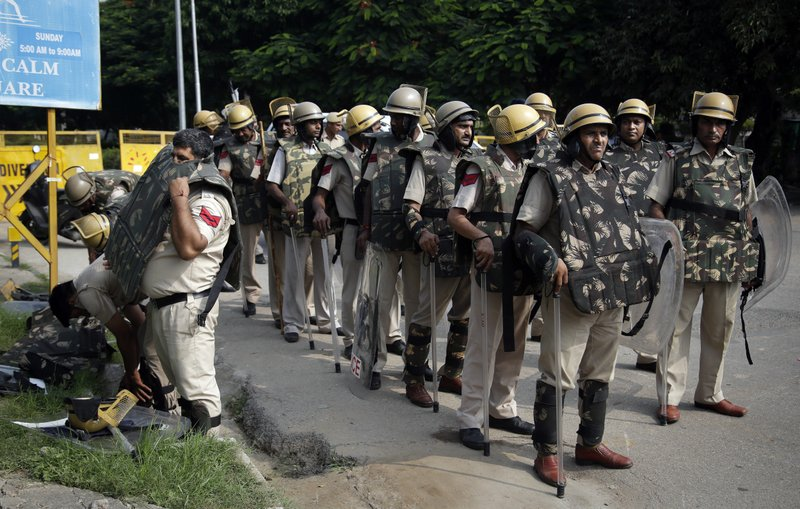 An Indian policeman puts on a bullet proof vest as he joins others on a road leading to a court in Panchkula, India, Friday, Aug. 25, 2017. Several north Indian cities were under a security lock down Friday as a court was expected to issue a verdict in a rape case involving a man who calls himself Saint Dr. Gurmeet Ram Rahim Singh Ji Insan, the flamboyant leader of a quasi-religious sect.