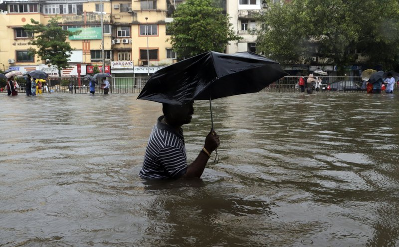 A man wades through a waterlogged street following heavy rains in Mumbai, India, Tuesday, Aug. 29, 2017. Heavy rains Tuesday brought Mumbai to a halt flooding vast areas of the city.
