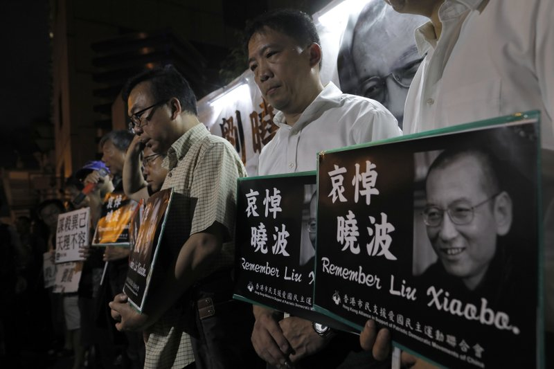 Protesters mourn jailed Chinese Nobel Peace laureate Liu Xiaobo during a demonstration outside the Chinese liaison office in Hong Kong, Thursday, July 13, 2017. Officials say China's most prominent political prisoner, Nobel Peace Prize laureate Liu Xiaobo, has died. He was 61.