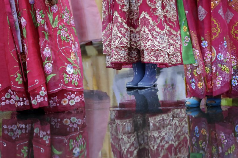 In this Thursday, July 27, 2017, file photo, a university student wears a pair of rain boots with her traditional Korean dress as she waits in the rain for the start of a mass dance, in Pyongyang, North Korea as part of celebrations for the 64th anniversary of the armistice that ended the Korean War.