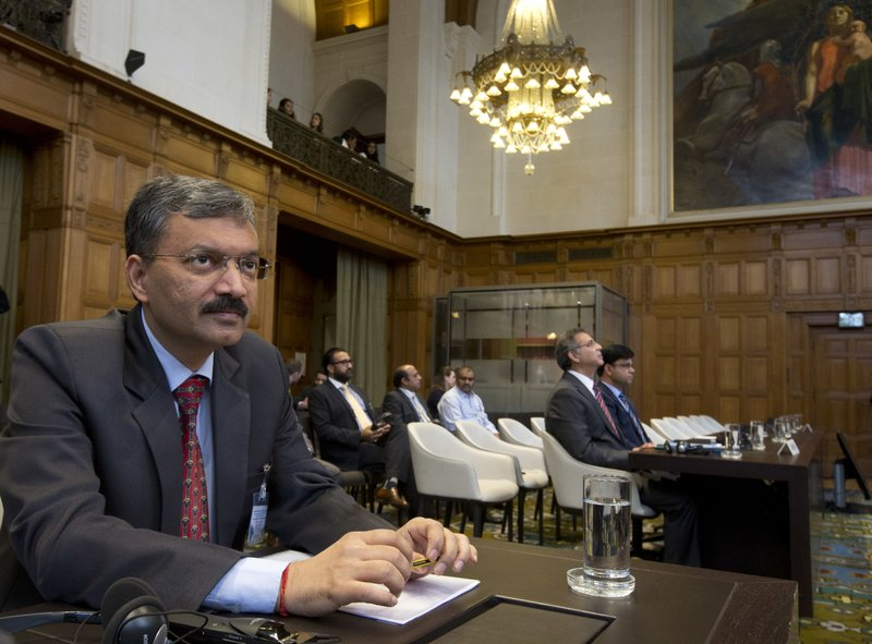 Dr. Deepak Mittal, joint secretary of India's Ministry of External Affairs, left, and Moazzam Ahmad Khan, head of Pakistan's delegation and ambassador, second right, wait for judges to enter and read the World Court's verdict in The Hague, Netherlands, Thursday, May 18, 2017. India took Pakistan to the United Nations' highest court in an attempt to save the life of an Indian naval officer sentenced to death last month by a Pakistani military court after being convicted of espionage.