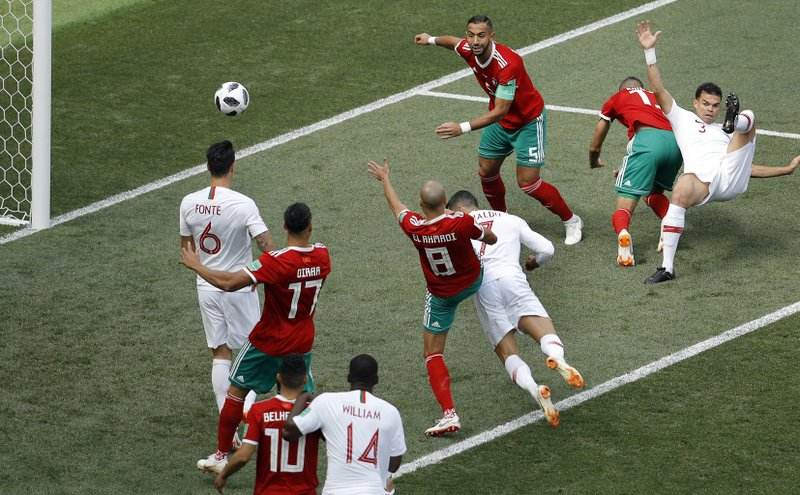 Portugal's Cristiano Ronaldo, center, heads the ball to score the opening goal during the group B match between Portugal and Morocco at the 2018 soccer World Cup in the Luzhniki Stadium in Moscow, Russia, Wednesday, June 20, 2018.
