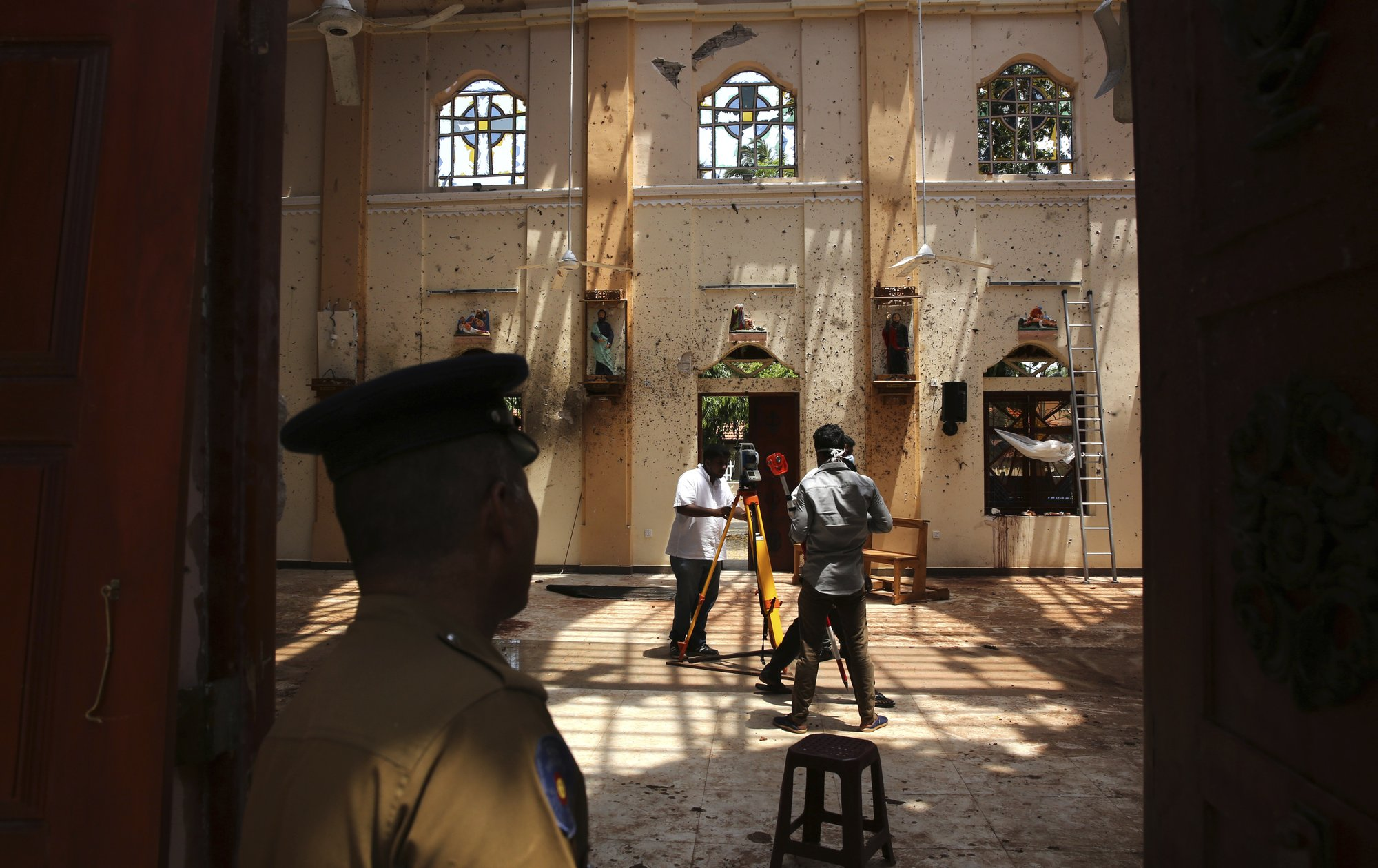 In this Thursday, April 25, 2019 photo, a policeman stands guard, as surveyors work at St. Sebastian's Church, where a suicide bomber blew himself up on Easter Sunday in Negombo, north of Colombo, Sri Lanka. Nearly a week later, the smell of death is everywhere, though the bodies are long gone. For more than 50 years, St. Sebastian's had been the scene of weddings and baptisms, of Christmas celebrations and countless Masses. The walls are now blackened near where the bomber stood when he killed himself, spraying shrapnel in every direction. (AP Photo/Manish Swarup)