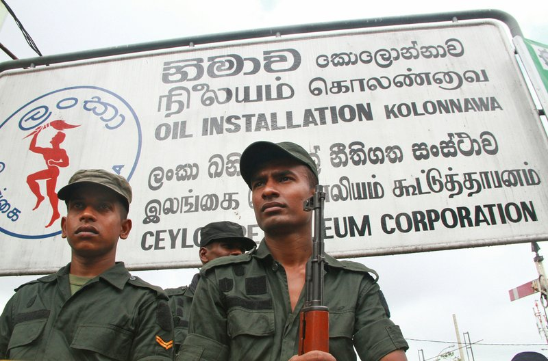 Army soldiers guard the main oil installation facility after taking the control back from protesting union workers in Colombo, Sri Lanka, Wednesday, July 26, 2017. Sri Lanka's government has deployed army troops to restore fuel distribution crippled during a strike launched by trade unions who want to stop leases of oil tanks to India and China.