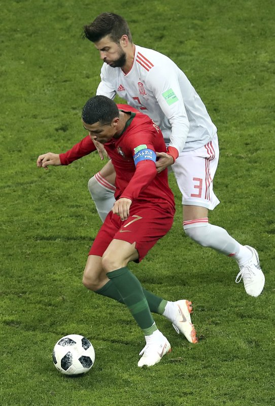 Portugal's Cristiano Ronaldo, front, and Spain's Gerard Pique, rear, challenge for the ball during the group B match between Portugal and Spain at the 2018 soccer World Cup in the Fisht Stadium in Sochi, Russia, Friday, June 15, 2018.
