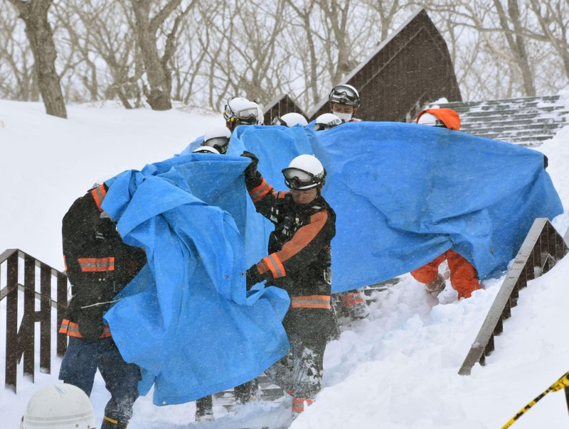 Rescuers carry the people who got injured in an avalanche at a ski resort in Nasu, Tochigi prefecture, Monday, March 27, 2017. Authorities said six Japanese high school students have been found unconscious after they were caught in the avalanche Monday morning.