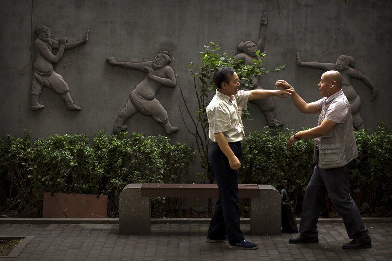 In this Wednesday, July 26, 2017, file photo, two men practice martial arts techniques at a public park in Beijing. Beijing is dotted with urban parks that offer a quieter, greener respite from the crowded streets of China's capital.