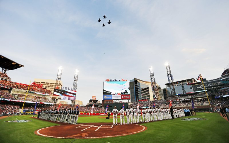 United States Navy fighter jets fly over SunTrust Park during the national anthem before a baseball game between the Atlanta Braves and the San Diego Padres in Atlanta, Friday, April 14, 2017. The Braves are playing their first regular-season game in SunTrust Park, the new suburban stadium that replaced Turner Field. (AP Photo/John Bazemore)