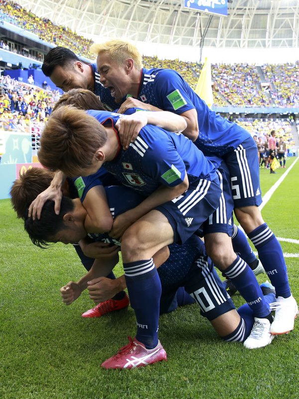 Teammates crowd over Japan's Shinji Kagawa after he scored from the penalty spot his side's first goal against Colombia during a group H match at the 2018 soccer World Cup in the Mordavia Arena in Saransk, Russia, Tuesday, June 19, 2018.