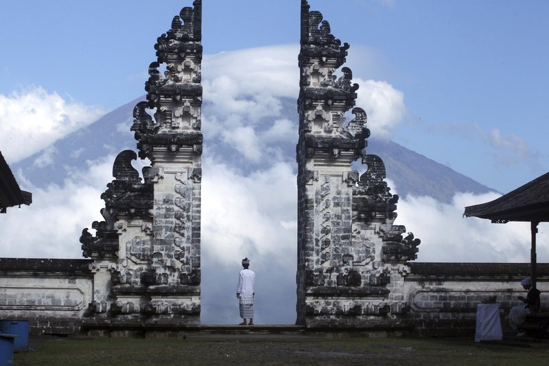 In this Tuesday, Sept. 26, 2017, file photo, a Balinese man watches Mount Agung volcano almost covered with clouds as he stands at a temple in Karangasem, Bali, Indonesia. An increasing frequency of tremors from the volcano indicates magma is continuing to move toward the surface and an eruption is possible, a disaster agency official said Tuesday. Tourists are cutting short their stay to the island, where an eruption would force the airport to close and strand thousands.