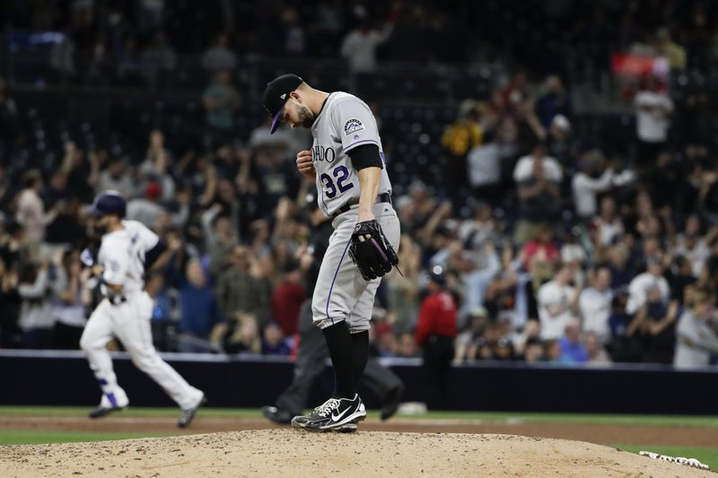 Colorado Rockies starting pitcher Tyler Chatwood (32) waits as San Diego Padres' Ryan Schimpf rounds the bases after hitting a home run during the sixth inning of a baseball game Tuesday, May 2, 2017, in San Diego. (AP Photo/Gregory Bull)