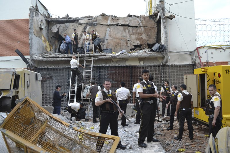 Guards and police inspect a vault that the assailants blew up early morning in Ciudad del Este, Paraguay, Monday, April 24, 2017. Dozens of attackers armed with assault rifles used explosives to blast open the vault of an armored car company early Monday and apparently escaped by boat into Brazil with a haul of cash, authorities said.
