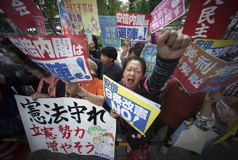"In this Thursday, Sept. 28, 2017, file photo, protesters gather in front of the Diet building after the lower house was dissolved in Tokyo. Japanese Prime Minister Shinzo Abe dissolved the lower house of parliament, paving the way for a snap election that is expected to be held on Oct. 22. The banner at top in the center reads: ""Abe cabinet, go out of office."""